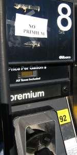 Paper printed No Primium sign above Premium gas pump nozzle